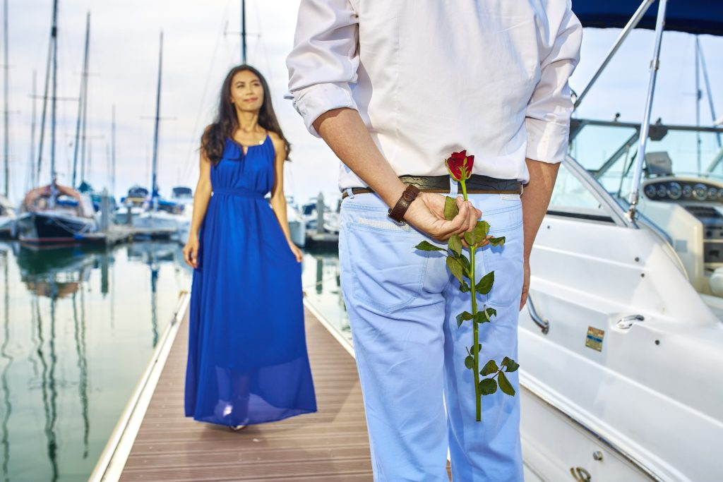 man holding a rose behind his back meeting a woman standing on a dock